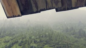 Mountains in rain and mist. Drops drip, wet and cold mountain atmosphere. Wooded hills in fog. Monumental clouds in sky. Big tree in foreground. Excursional stock footage