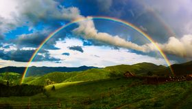 Mountains and rainbow. Beautiful mountain valley with green hills and huge rainbow in summer. Natural outdoor travel background. Carpatians, Ukraine Stock Image