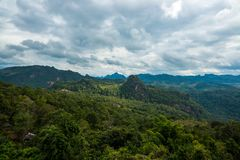 Mountains range view behind the mist of forest and tree Royalty Free Stock Images