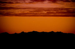 Mountains with red sunset. Rocky Mountains with orange sunset with chinook clouds that happen in Calgary Alberta Royalty Free Stock Photo