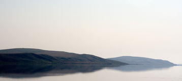 Mountains reflected in the sea Stock Photography