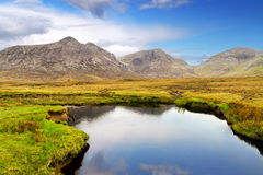 Mountains reflected in small lake. Connemara mountains and lake scenery, Ireland Stock Photo