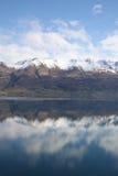 Mountains reflected in still lake. Beautiful reflection of Eyre Mountain range in Lake Wakatipu New Zealand Royalty Free Stock Photos