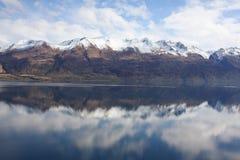 Mountains reflected in still lake. Beautiful reflection of Eyre Mountain range in Lake Wakatipu New Zealand Stock Photos