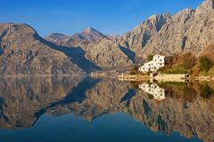 Mountains reflected in the water of Bay of Kotor on calm winter day. Montenegro, Dobrota. Mountains reflected in the water of Bay of Kotor Adriatic Sea on calm Royalty Free Stock Photography