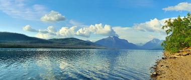Mountains and reflection of clouds in McDonald lake in Glacier National Park Royalty Free Stock Photography