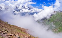 Mountains Ridges Clouds. Majesty of nature: great view of the foggy valley. Clouds covered the mountain ridges Stock Image
