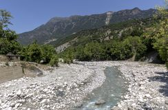 The mountains and the river Kalarrytikos on a sunny summer day royalty free stock image