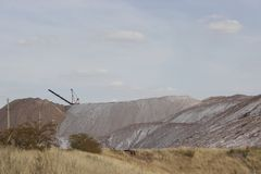 Mountains of salt and a crane upstairs. Extraction of minerals stock photos