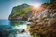 Mountains and sea scenery with blue sky and bright sun rays over Royalty Free Stock Images