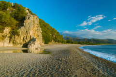 Mountains on sea shore under blue sky Stock Photography