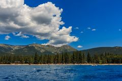 Mountains seen across the water from the boat on Lake Tahoe in California, USA. Mountains seen on shore across the crystal clear blue water, from the boat on stock photos