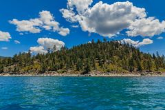 Mountains seen across the water from the boat on Lake Tahoe in California, USA. Mountains seen on shore across the crystal clear turquoise water, from the boat royalty free stock images