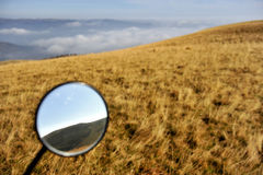 Mountains are seen in a motorcycle mirror Stock Images