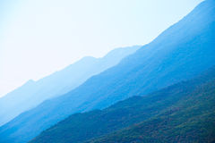 Mountains shrouded in bluish mist Stock Images