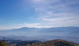 Mountains silhouette through mist with beautiful horizon. stock images