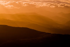 Mountains silhouette at sunset with fog Royalty Free Stock Image