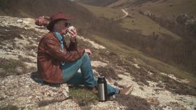 In the mountains sits a man in a cowboy hat, leather jacket, blue jeans and glasses. A man drinking tea from a thermos. Background of mountains and sky stock footage