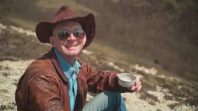 In the mountains a man in a cowboy hat, leather jacket, blue jeans and glasses. The man looks at the frame and smiles. In the mountains sits a man in a cowboy stock video