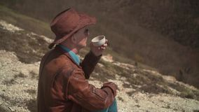 In the mountains sits a man in a cowboy hat, leather jacket, blue jeans and glasses. A man drinking tea from a thermos. Background of mountains and sky stock video footage