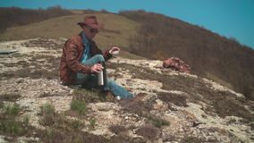 In the mountains sits a man in a cowboy hat, leather jacket, blue jeans and glasses. A man pours himself tea. In the mountains sits a man in a cowboy hat stock video footage