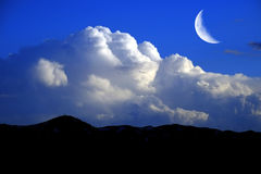 Mountains sky billowy white thunder clouds and crescent moon Royalty Free Stock Photography