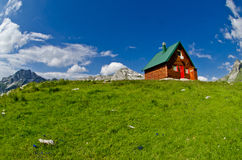 Mountains and small wooden house on green field, Zabljak, Montenegro Royalty Free Stock Photos
