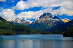 Mountains with snow above blue lake Stock Photo