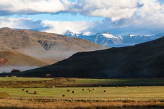 Mountains Snow Farm Field Grass Bales Stock Image