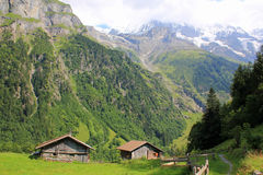 Mountains with snow, hiking path and cabins, Switzerland. Lauterbrunnen valley in Switzerland. View at mountains with snow, hiking path and cabins. Mountain royalty free stock image