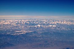 Mountains with snowy peaks on blue sky, aerial view. Planet earth natural landscape. Travel around world. Environment. Protection and ecology. Earth day is royalty free stock image