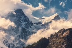 Mountains with snowy peaks in clouds at sunset Royalty Free Stock Images