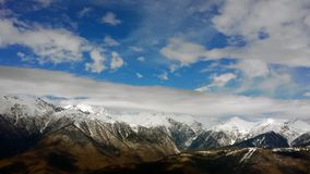 Mountains with snowy peaks and sky. With clouds royalty free stock photos