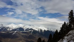 Mountains with snowy peaks and sky. With clouds royalty free stock images