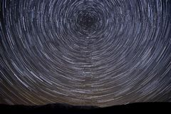 Mountains star tracks sky revolve. A beautiful night panorama of the starry sky with traces of stars in the form of circular tracks revolving around the polar Stock Images