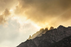 Mountains stone peaks with orange clouds under sunset light. Stock Photo