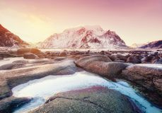 Mountains, stone, water and sunrise on Lofoten islands, Norway. Natural landscape in the Norway. Sunrise on the seashore and reflection on the water surface stock image