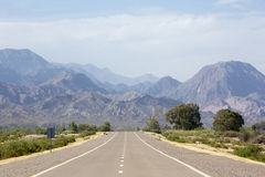 Mountains and straight road 40 in Argentina. The famous Route 40 paved road parallel to the Andes against a blue sky and going towards the Ischigualasto National Stock Photography