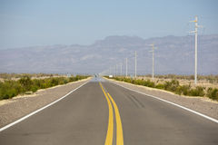 Mountains and straight road 40 in Argentina. The famous Route 40 paved road parallel to the Andes against a blue sky and going towards the Ischigualasto National Royalty Free Stock Photography