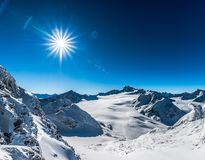 Mountains, sun with flare. A series of hills or mountains, blue clear sky, beautiful sun with flare. Solden, Austria Royalty Free Stock Photography