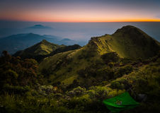 Mountains during sunrise. Photo of mountains and dormant stratovolcano, Mount Merbabu, covered with fog during sunrise near Yogya in central Java province in Royalty Free Stock Photo