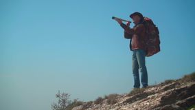 A man in a cowboy hat, leather jacket, blue jeans, a tourist backpack on his shoulders. A man looks through a telescope. In the mountains there is a man in a stock video