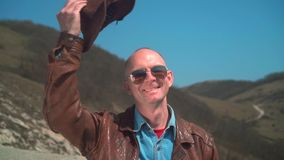 A man in a cowboy hat, leather jacket, glasses. A man puts his hand to his hat and takes off his hat. In the mountains there is a man in a cowboy hat, leather stock video footage