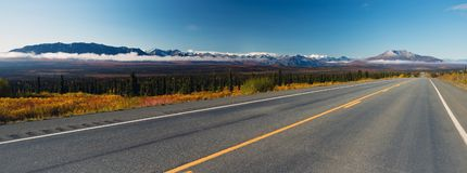 Mountains To Tundra Valley View Two Lane Highway Alaska United States. Mountains in an Alaskan Range stand above the clouds rising from the Valley Stock Photos