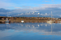 Mountains and town Ushuaia reflecting in water, Patagonia Stock Photography