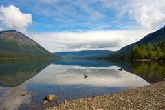 Mountains and trees reflected in a calm lake along the cassiar highway stock image