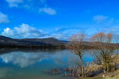 Among the mountains and trees there is a small blue lake. In which ducks swim, the blue sky is covered with spring clouds and reflected on the water surface Royalty Free Stock Image