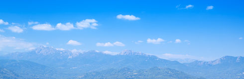 Mountains under bright cloudy sky. Corsica. Panoramic natural photo background with mountains under bright cloudy sky. Corsica, France Royalty Free Stock Photography