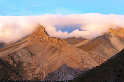 Mountains under the clouds. Pink mountains under the clouds Stock Image