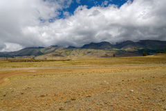 Mountains valley dirt road clouds Royalty Free Stock Image